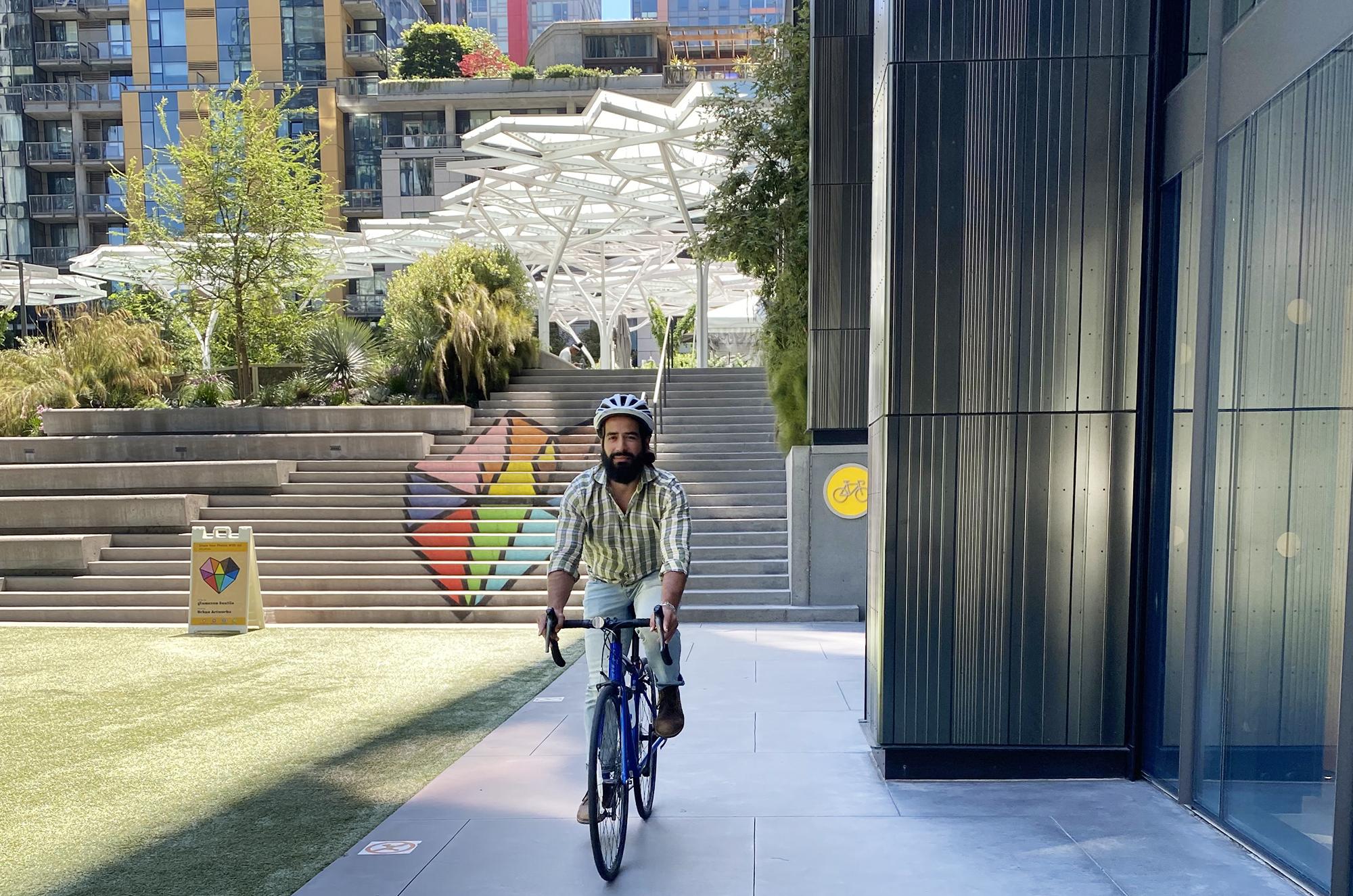 A man rides a bike wearing a helmet through the Amazon HQ in Seattle.