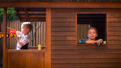Two toddlers play inside of a wooden playhouse.