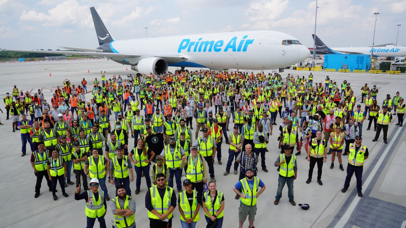 An image of more than 100 employees wearing their safety vests while standing in front of a Prime Air plane at the Kentucky Air Hub.
