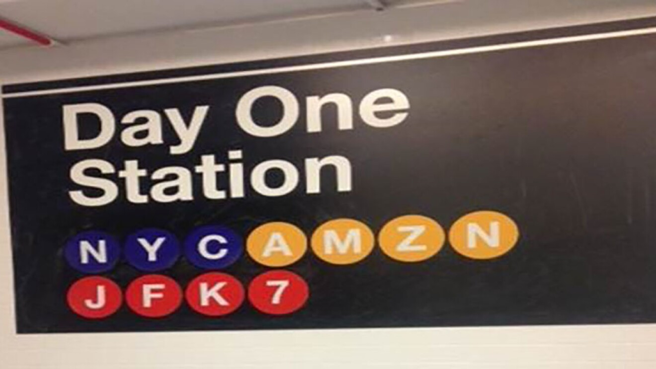 """An image of a NYC subway station sign that says """"Day One Station, NYC AMZN JFK7"""""""
