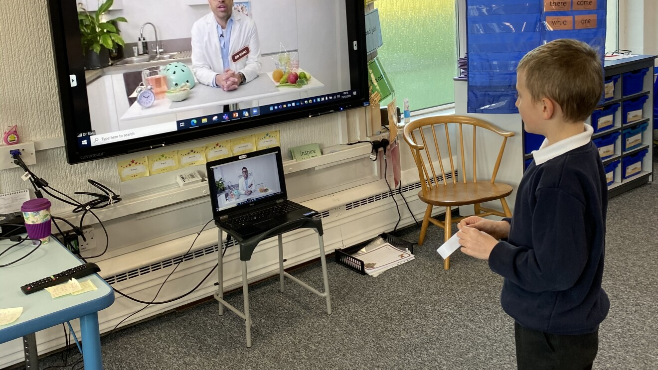 An image of a boy at school looking at a television with an instructor on it.