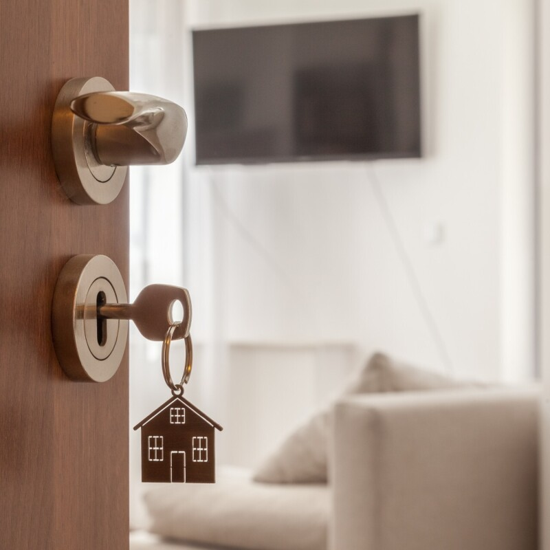 Open door to a new home. Door handle with key and home shaped keychain.