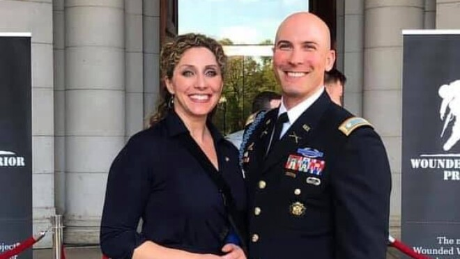 An image of a couple smiling for a photo outside of a building with red ropes in front of it. The man is wearing a military outfit and there are signs for Wounded Warrior Project behind them.