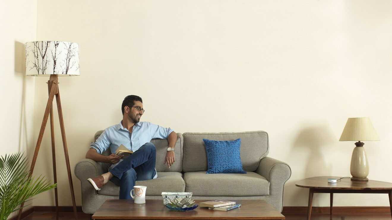 A man sits on a sofa in what looks like he is interacting with Alexa