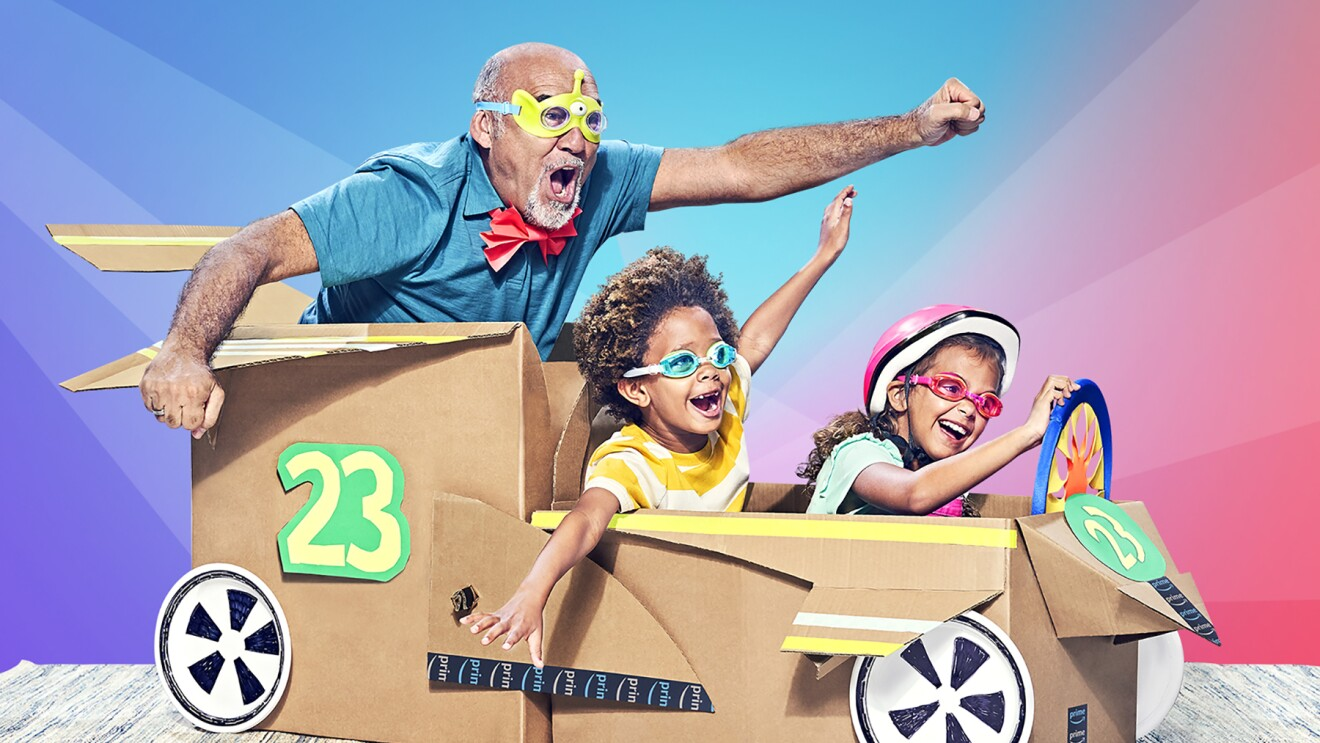 "Two children and a man appear joyful as the ""ride"" in a cardboard box car."