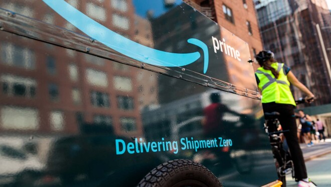 """An Amazon delivery person riding a bicycle, with a bike trailer behind it. The trailer has """"Delivering Shipment Zero"""" printed on it."""