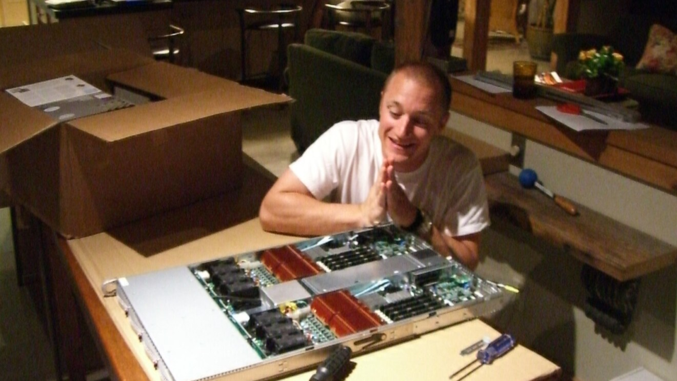 An image of a man holding his hands in a prayer position while sitting next to a server he just built.