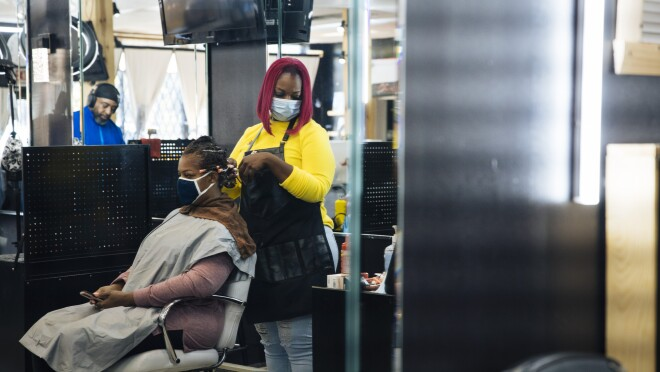 Inside her salon, Auhzha Wright styles a client's hair while both are wearing face coverings