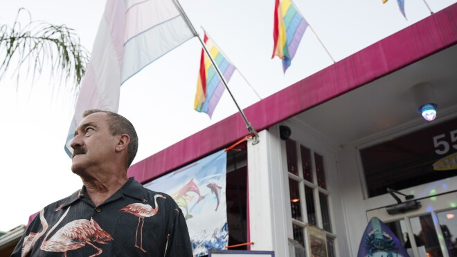 A man stands in front of a building flying gay pride and transgender pride flags.