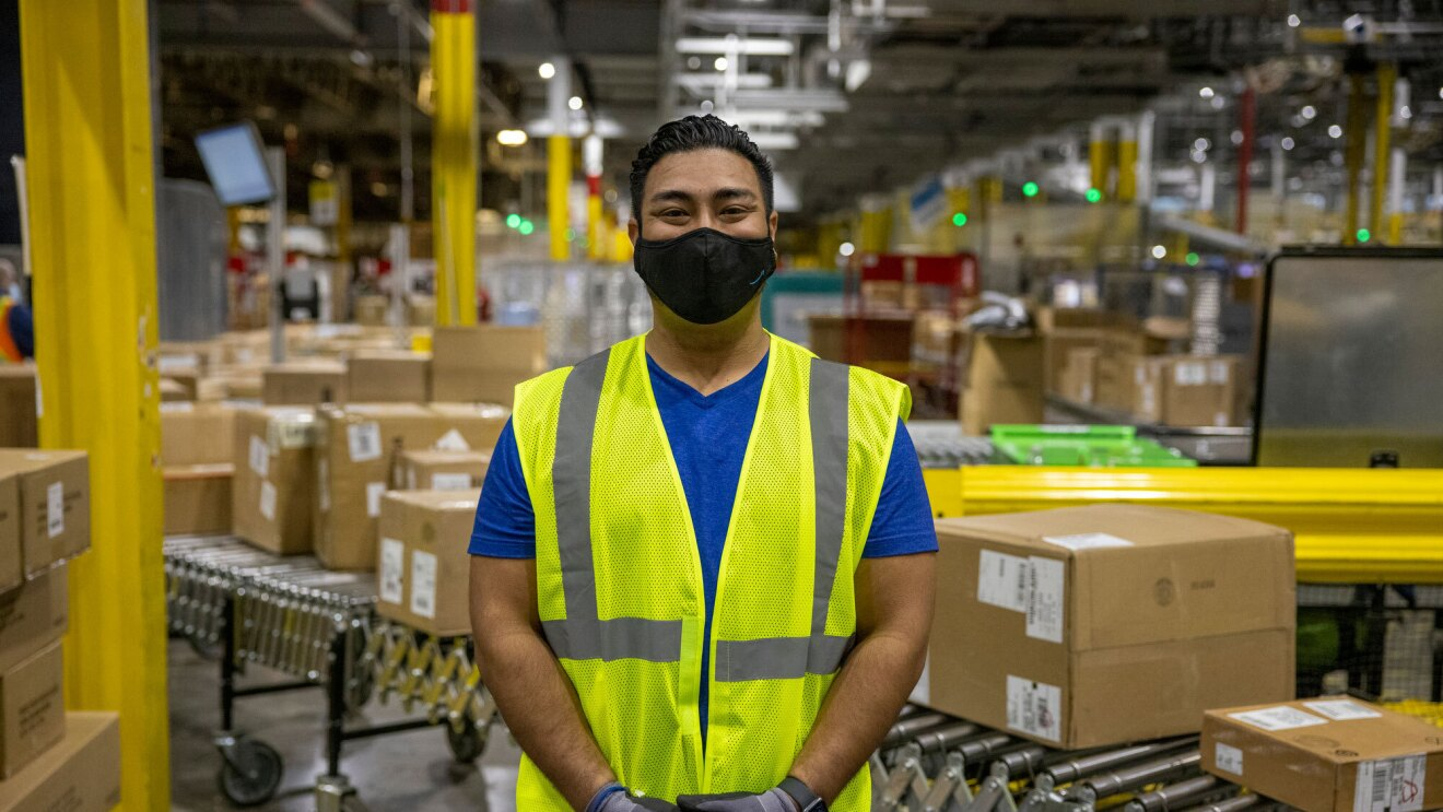 A male employee wearing a face mask and a yellow safety vest stands on the floor of an Amazon fulfillment center, looking at the camera. Boxes are on a conveyor belt behind him.