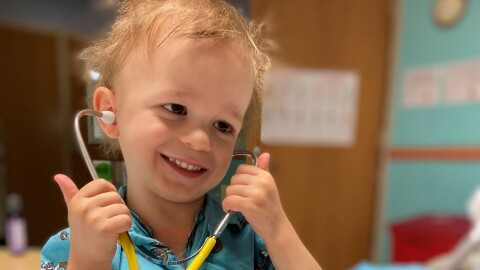 An image of a young boy smiling while hold a stethoscope to his ears.