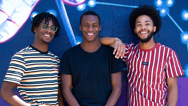 Three AfroPick founders stand side-by-side in front of art.