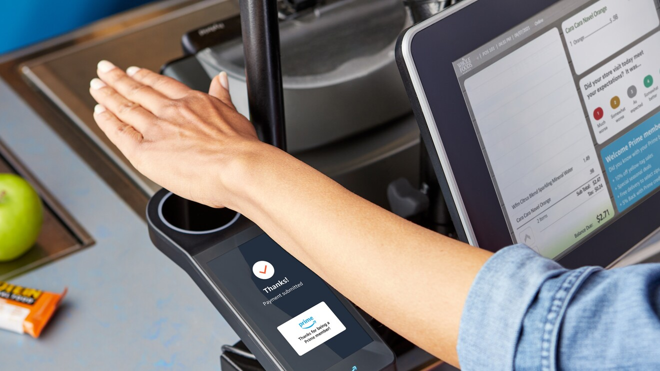 A hand hovers over a scanner at a grocery store, allowing a woman to check out and purchase her items.