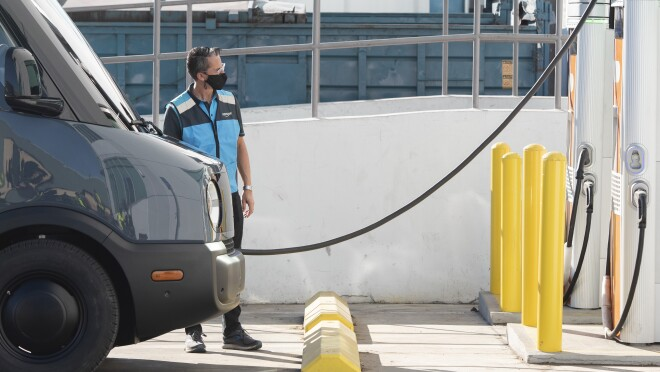 An Amazon-branded Rivian van gets charged at an electric station.