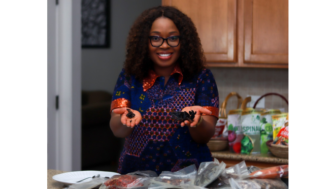 Toyin Kolawole, CEO, Iya Foods holds up some of her product while she smiles for the camera. In front of her and behind her are bags of her product. She wears a blue patterned dress with an orange collar and sleeves. She has dark curly hair to her shoulders and wears black-framed eyeglasses.