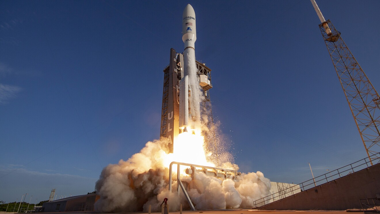 """An image of a satellite launching. It has """"Amazon"""" and the American flag decaled on the side. There is a blast below the satellite indicating launch and a blue, evening sky in the background."""
