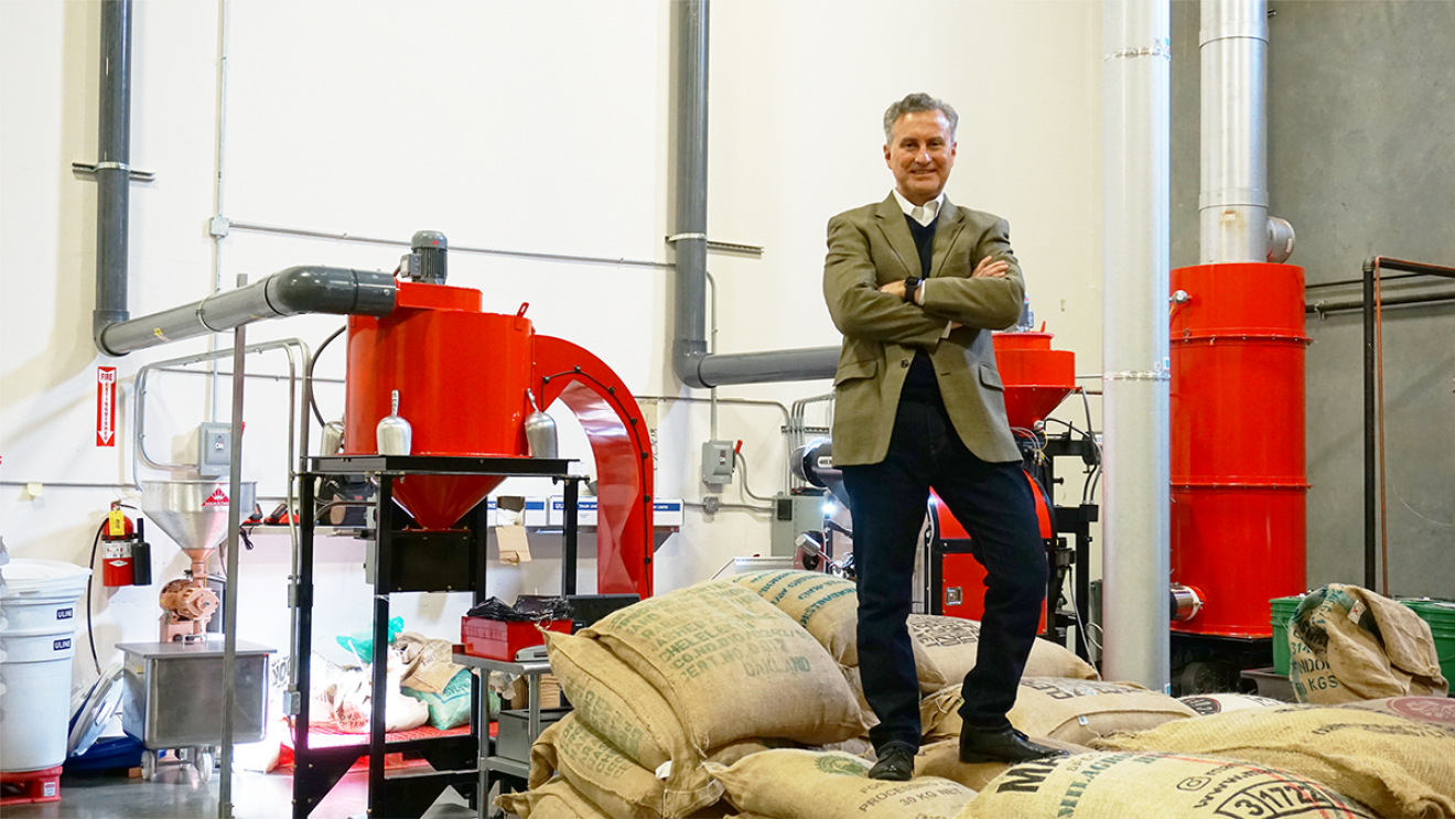 An image of a man standing on a pile of burlap sacks filled with a product in a factory.