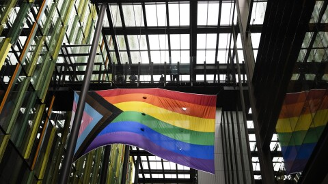 An image of the new Progress Pride flag flying in the breezeway of one of Amazon's offices at its Seattle headquarters. The flag features the rainbow on the right and a triangle with light pink and blue and black and brown on the left.