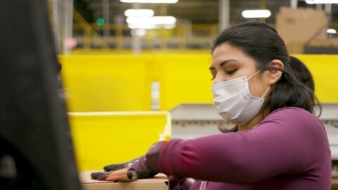 Amazon employee performing work duties while wearing a mask during the COVID-19 pandemic.