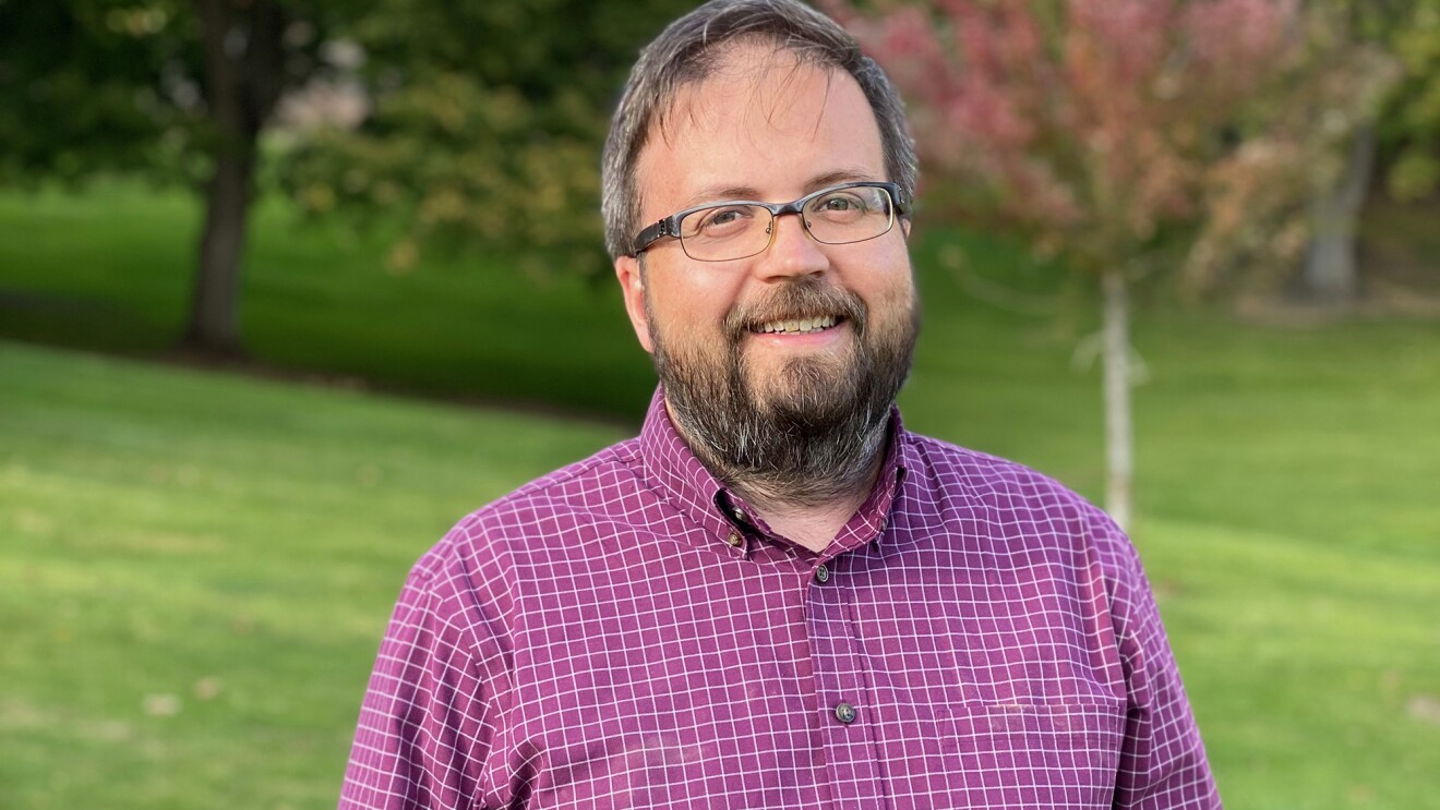 A man smiles at the camera. He wears glasses and a button down, and stands in a park setting.