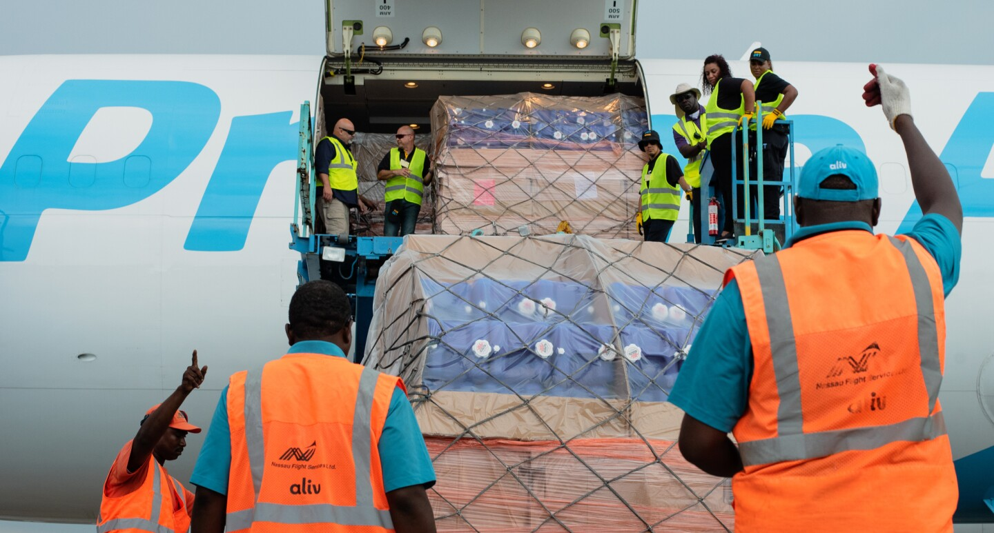 Employees in orange and yellow vests lift cargo supplies onto a Prime Air plane.