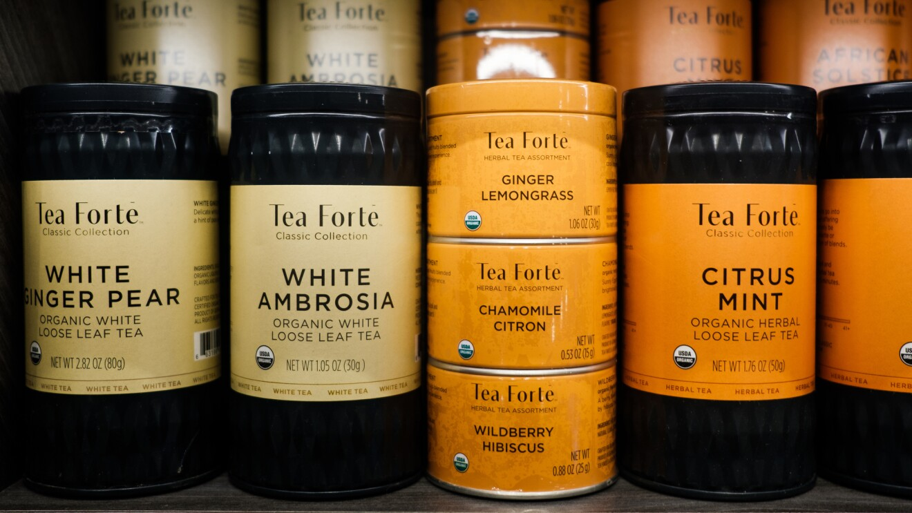 Canisters of Tea Forté tea sit on a shelf. Products shown include white ginger pear, white ambrosia, ginger lemongrass, chamomile citron, wildberry hibiscus, and citrus mint.