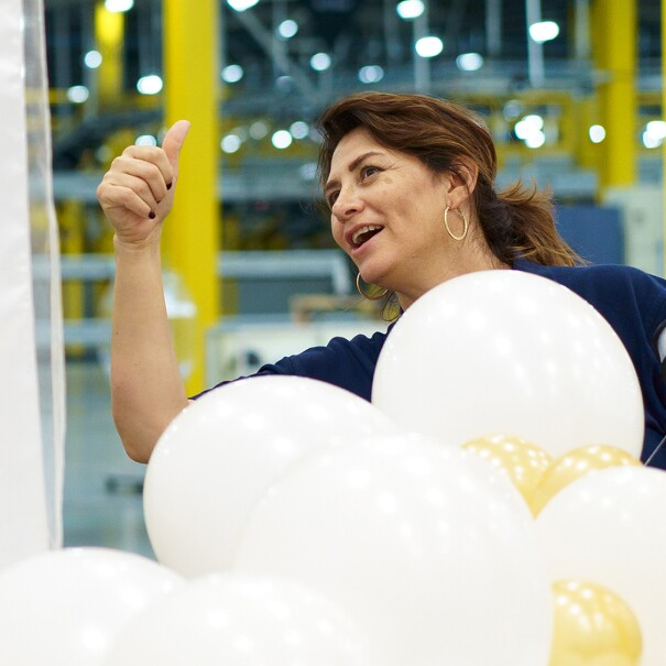 Woman gives a thumbs-up sign while assembling decorative balloons.