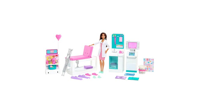 an image of a Barbie doll in a white doctor's coat. She is standing among a setup of a clinic with different medical devices and equipment.