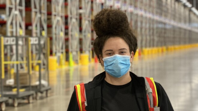 A woman wearing a safety vest and a mask stands in a warehouse space.