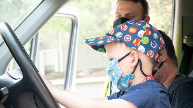 An image of a boy in the driver's seat of a van. He is pretending to drive and sitting next to his father. Both are wearing masks.
