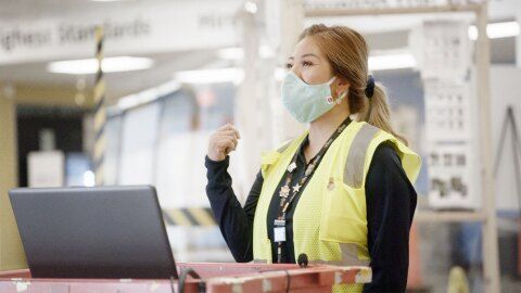 Amazon associate Christine P wears a mask and safety vest at her rolling laptop work station inside an Amazon fulfillment center