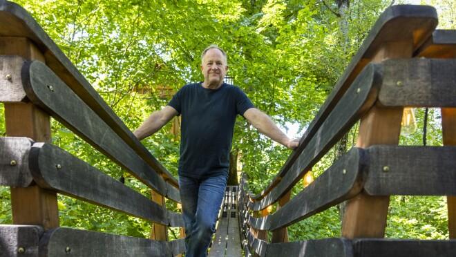A man stands on an aerial footbridge.