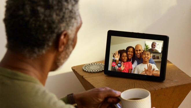An Echo Show device on a wooden side table. On the screen, a family of four are smiling and waving on the screen. Facing the device is a man, holding a coffee cup. The screen shows his smiling face.