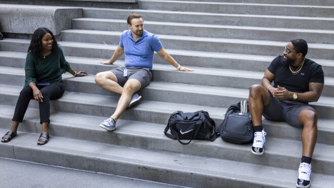 A woman and two men sit on a concrete staircase.