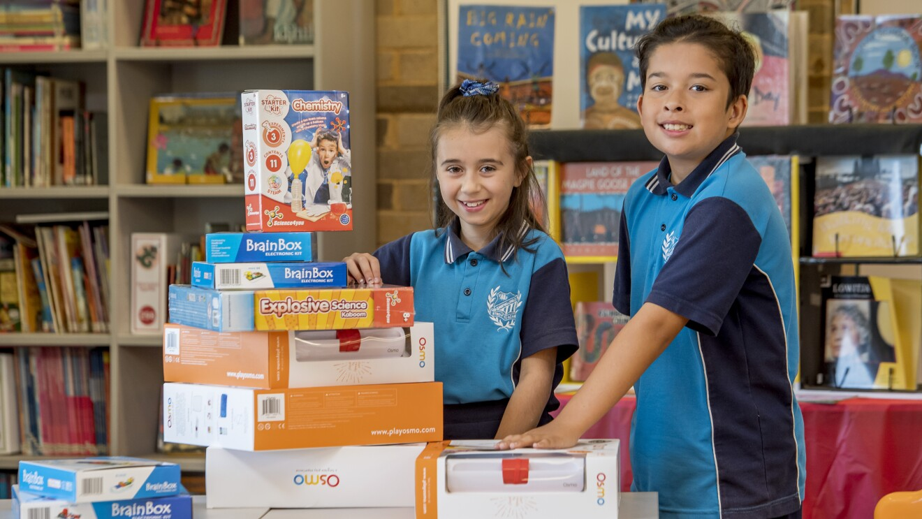 Two children smile as they stand behind a stack of STEM toys in a school library.