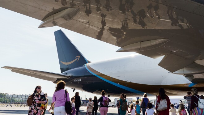 The wing of a golden Prime Air aircraft wing reflects children and their parents at an Amazon event supporting childhood cancer awareness. The aircraft tail is visible, with a gold Amazon smile.
