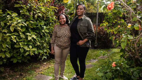 Kimberly and her mom stand next to one another with their arms around each other. They stand in a beautiful, green, luscious backyard. Kimberly is wearing black pants with a black shirt and an olive green jacket. Her mom wears khaki pants and a leopard top.