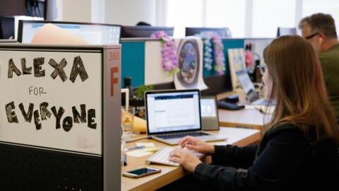 """Two people sit at their desks which are side-by-side. There is a white board that reads """"Alexa for everyone"""""""