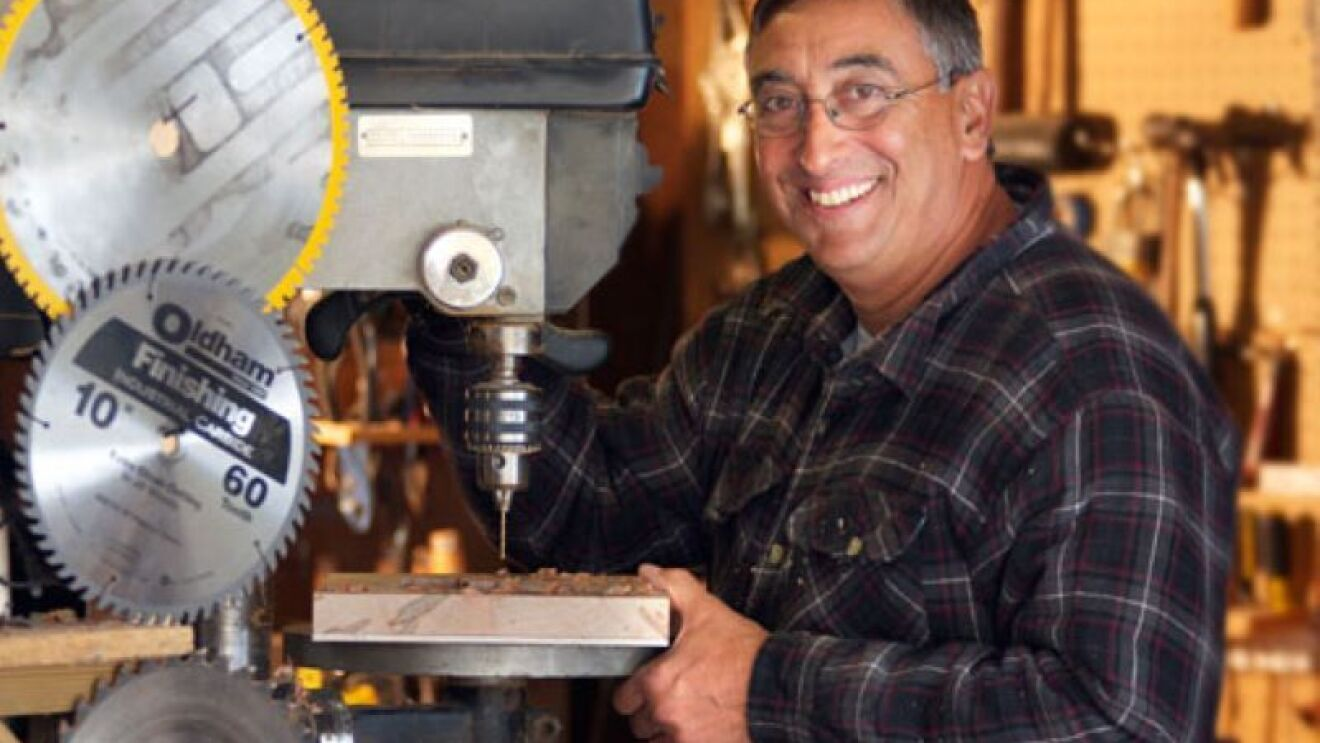 A man stands next to an electric saw and smiles at the camera