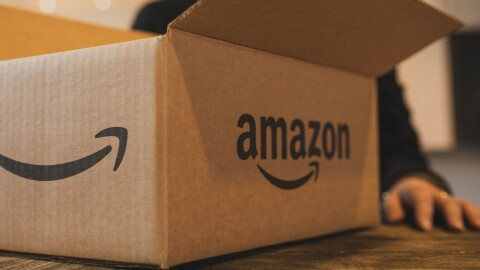 A box with an Amazon smile on it. A woman's hand is visible behind the box.