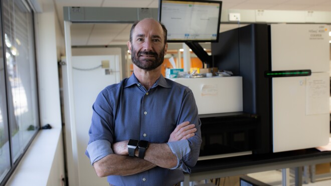 Michael Snyder, PhD, professor and chair of genetics for Stanford University's School of Medicine is wearing a blue button up with his sleeves rolled up and stands with his arm crossed wearing two smart watches. He stands in his labs with white boards and monitors behind him.