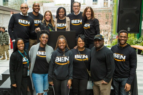 Members of the Black Employee Network stand for a photo on a podium on the steps of Amazon's Seattle headquarters.