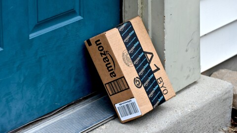 An Amazon package leans against the front door of a house.