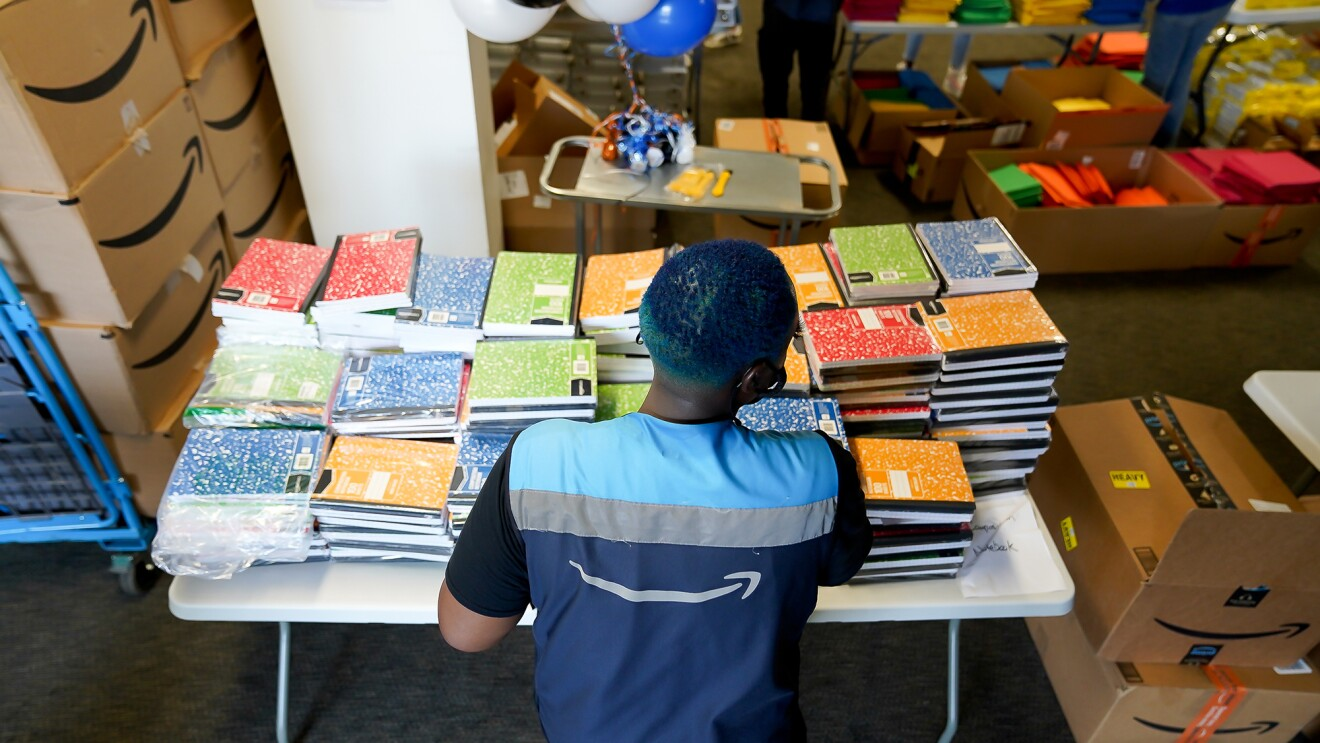 An Amazon employee stands in front of a table covered with composition and other school supplies.