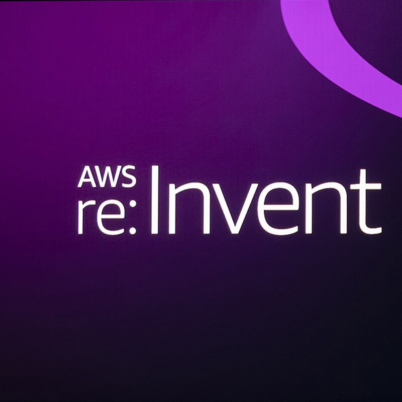 AWS re:invent logo on a purple gradiant background. To the right of the logo, streams of aqua and purple move appear to move fluidly across the image.