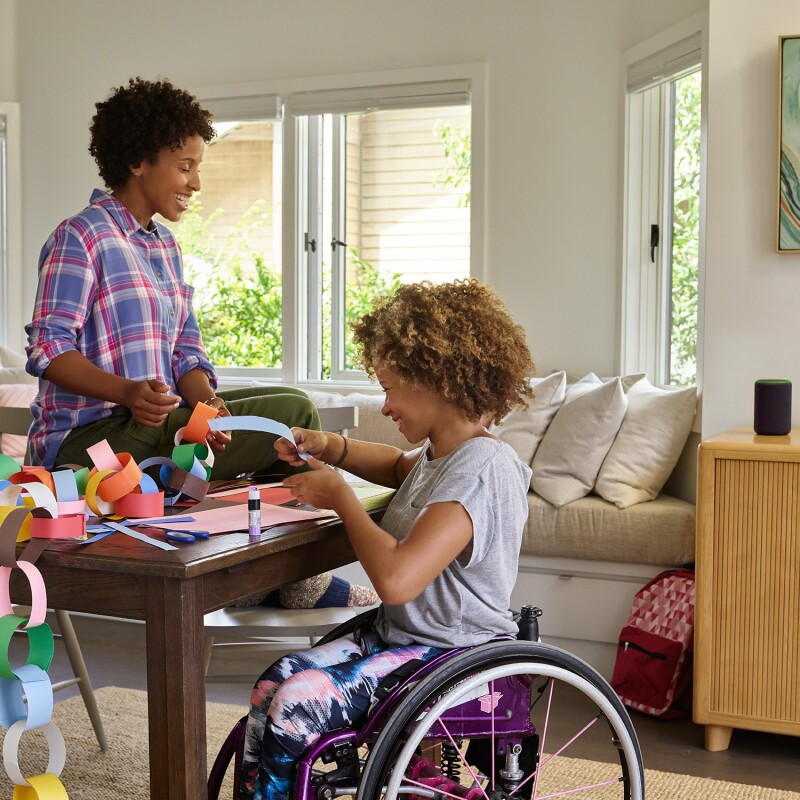A mother sits on a dining room table as she and her daughter laugh while making a paper chain. Behind them, Amazon Echo is on a console table.