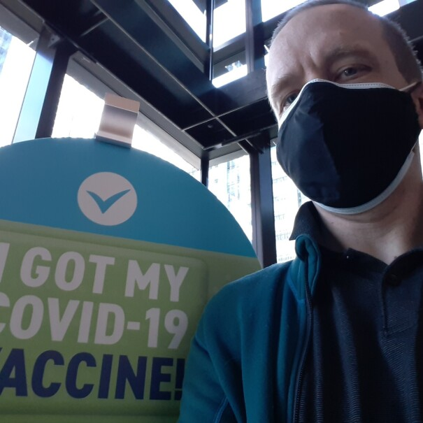 """A man wearing a mask and a collared shirt sits in front of a sign that says """"I got my COVID-19 vaccine."""""""