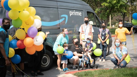 An image of a family smiling for a photo in front of an Amazon van. There are balloons and Amazon employees in the photo as well.