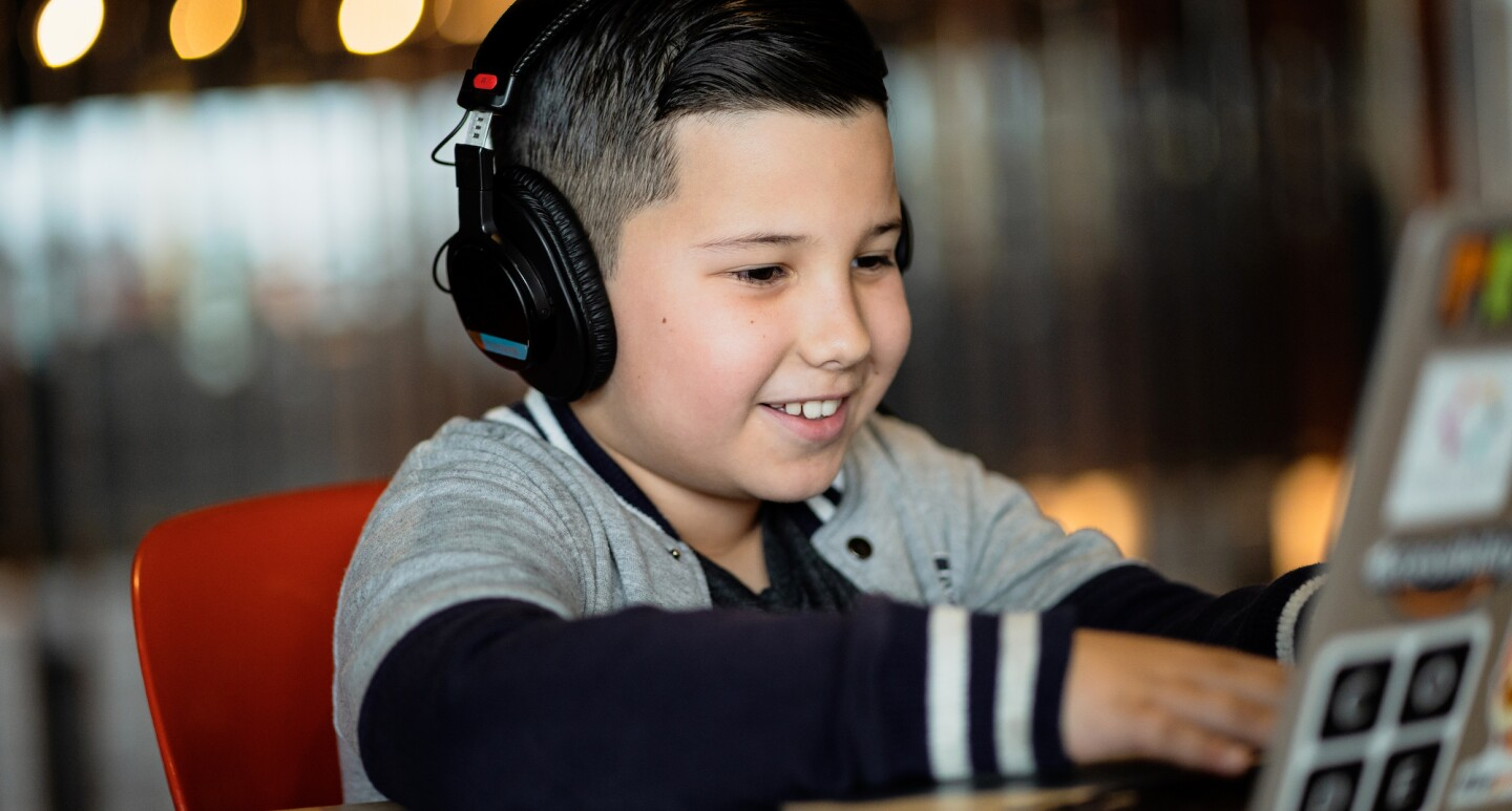 A boy wearing headphones works on a laptop at a coding camp while smiling.