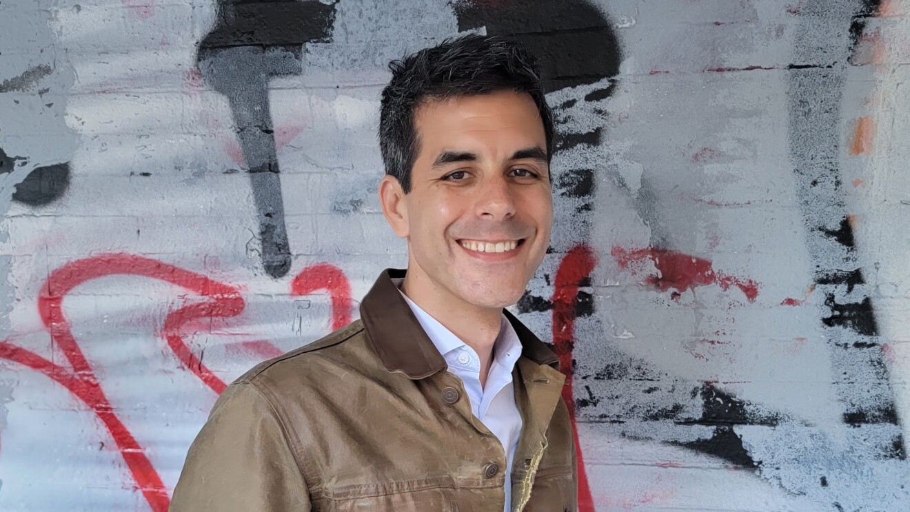 Adam Siegel smiles wearing a tan jacket and stands in front of a graffiti wall.